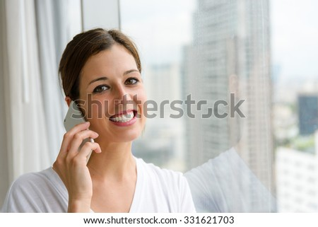 Woman on phone call at home near the window. Happy female using smartphone and smiling.