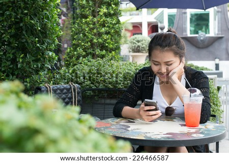 woman on phone drinking strawberry juice sitting outdoor in tren