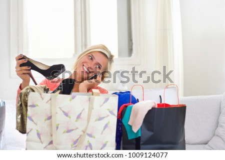 Woman on phone holds new shoes at home