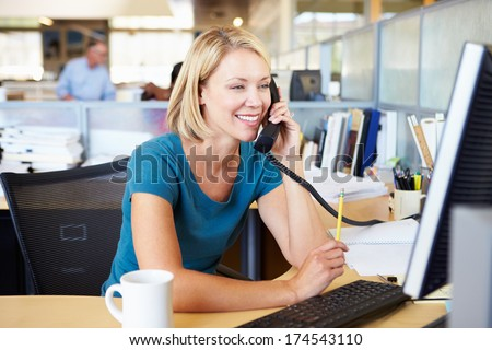 Woman On Phone In Busy Modern Office - stock photo