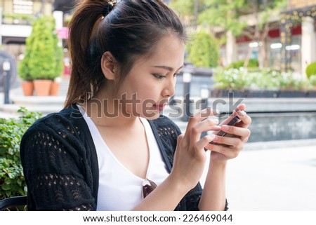 woman on phone sitting outdoor in trendy urban cafe.