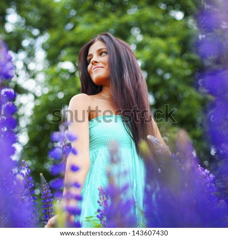 woman on pink flower field close portrait - stock photo