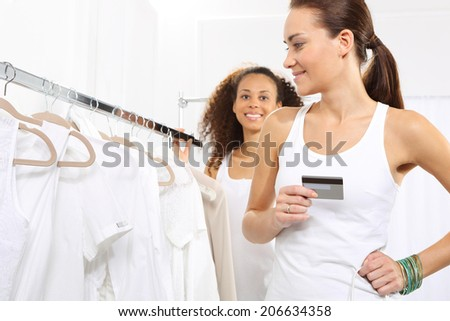 Woman on purchases paid by credit card.Woman in clothing store pay for purchases by credit card.  - stock photo