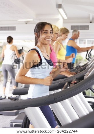 Woman On Running Machine In Gym - stock photo
