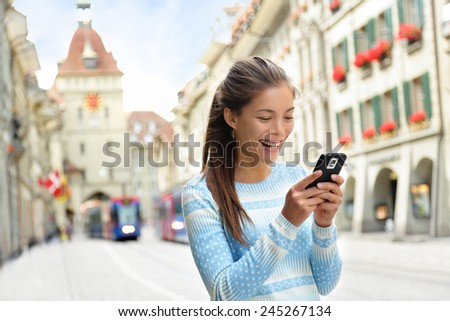 Woman on smart phone walking on Kramgasse, Berne main street in the old city. Young female using smartphone app visiting tourist attractions and landmarks. - stock photo