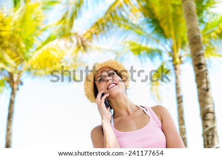Woman on summer tropical caribbean vacation talking on smartphone under palm trees. Beautiful young lady on holidays using calling on cellphone. - stock photo