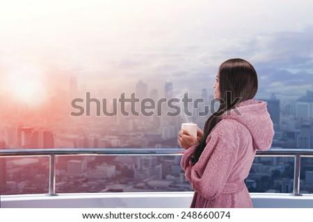 Woman on the balcony enjoying city view - stock photo