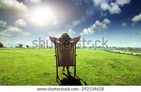 Woman on the beach area admiring the sea - stock photo