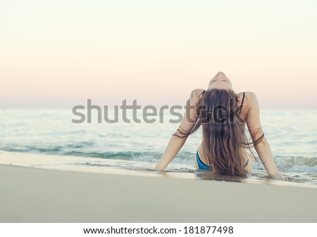 Woman on the beach at sunset. Vintage effect. - stock photo