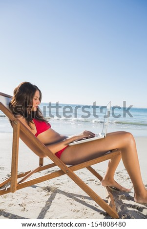 Woman on the beach using her laptop while relaxing on her deck chair