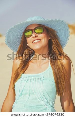 Woman on the beach with blue hat