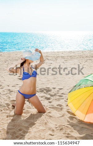 Woman on the beach. Young beautiful girl on the sand by the sea.