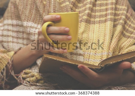Woman on the bed with old book and cup of coffee in hands, top view point. Copy space for text. Soft photo - stock photo