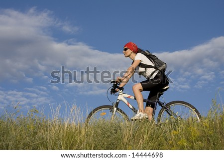 woman on the bicycle in the grass meadow