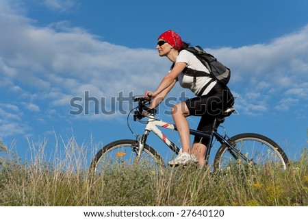 woman on the bicycle on the grass meadow