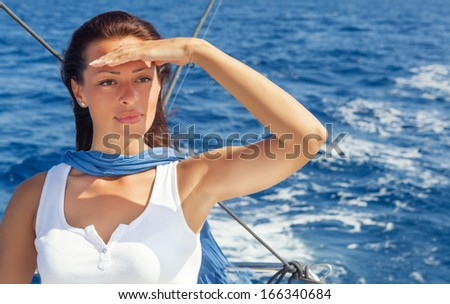 Woman on the bow of a Sailboat enjoying summer sailing and looking away.Copy space - stock photo