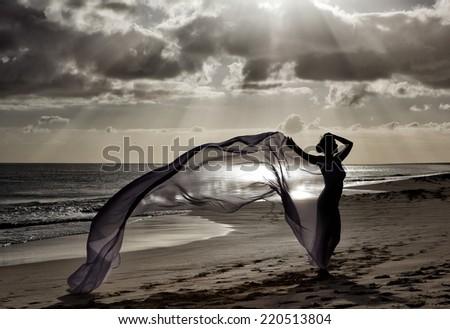 Woman on the ocean beach at Sundown as a Silhouette against the evening sky - stock photo