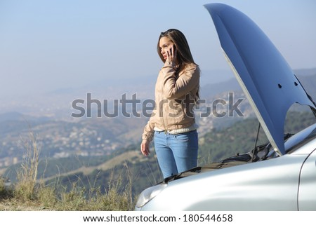 Woman on the phone asking for help beside her crash breakdown car in a road with a city in the background - stock photo
