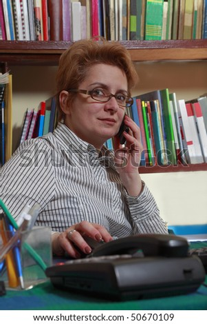 Woman on the phone at her home business desk. - stock photo
