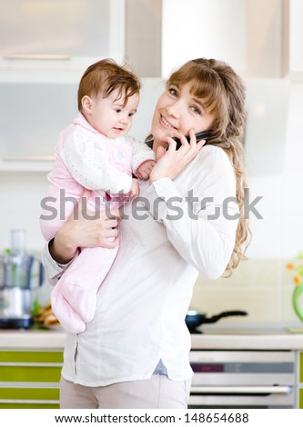 woman on the phone while holding her baby in her arms in the kitchen  - stock photo