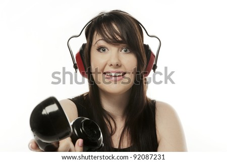woman on the phone with ear defenders on so she cant hear what the person on the other end of the phone has to say