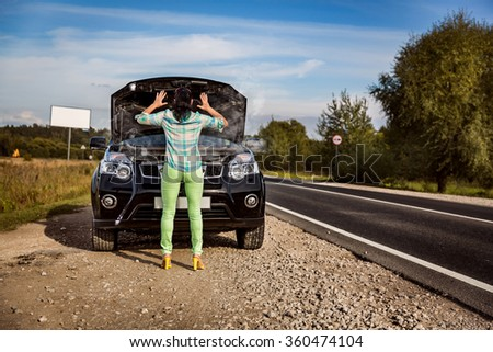 Woman on the road near the car. Damage to vehicle problems on the road. - stock photo