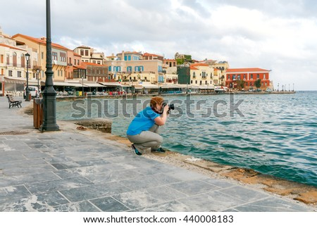 Woman on the waterfront of Chania photographs the old Venetian harbor.