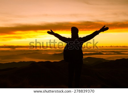 Woman on top a mountain with arms outstretched.  - stock photo