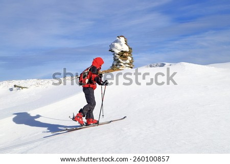 Woman on touring skies casts long shadow on snow covered mountain in sunny day of winter