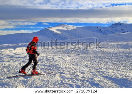 Woman on touring skies traversing a snow covered plateau on the mountain - stock photo