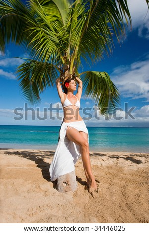 woman on tropical beach leaning on palm tree in white sarong and bikini relaxing in sun maui, hawaii
