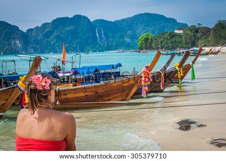 Woman on Tropical beach relaxing and watching longtail boats, Andaman Sea, Thailand - stock photo