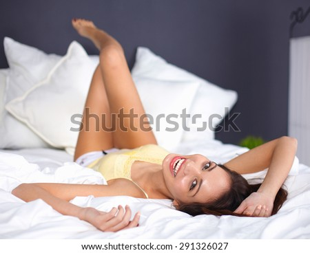 Woman on underwear is lying in the comfortable bed