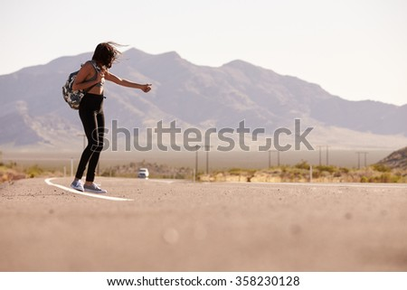 Woman On Vacation Hitchhiking Along Country Road - stock photo