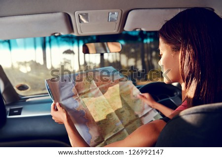 Woman on vacation looking at map for directions while driving in car