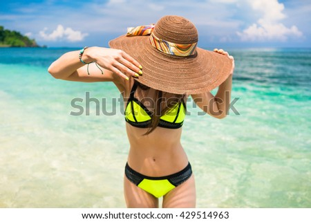 Woman on vacation wearing beach hat bathing in the ocean, face hidden