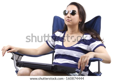 woman on vacation with laptop sitting on a beach chair
