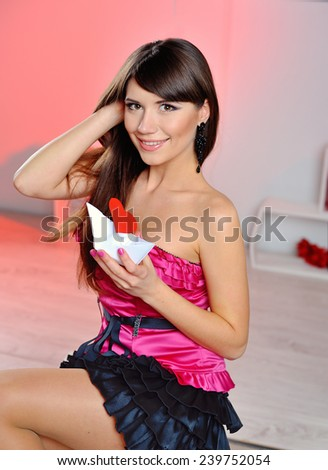 woman on Valentine's Day with a white paper a ship with a heart. - stock photo