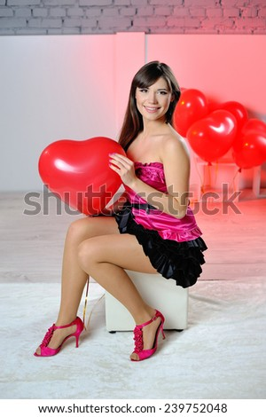 woman on Valentine's Day with red balloons in the shape of heart. - stock photo