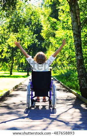 woman on wheelchair with her hands up in the park