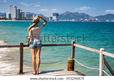 Woman on wooden pier admiring beautiful sea view, away from big city - stock photo