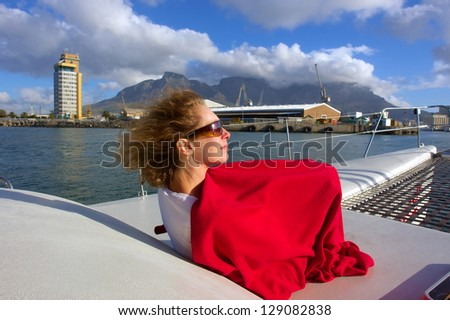 Woman on yacht's desk enjoys sunset light. Shot near Waterfront, Cape Town, Western Cape, South Africa. - stock photo