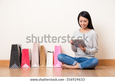 Woman online shopping though tablet pc