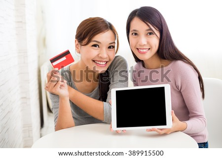 Woman online shopping with tablet pc and credit card - stock photo