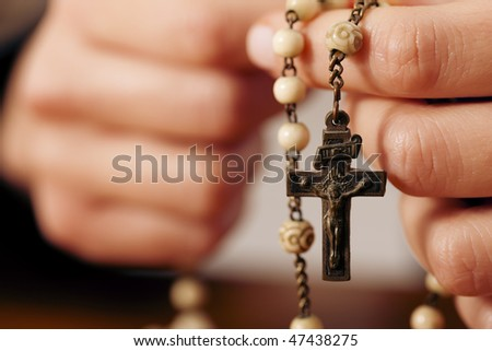Woman (only closeup of hands to be seen) with rosary sending a prayer to God, the dark setting suggests she is sad or lonely - stock photo