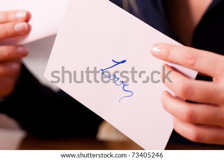 Woman � only hands to be seen -  is holding a love letter - stock photo