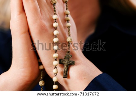 Woman (only hands to be seen) with rosary sending a prayer to God - stock photo