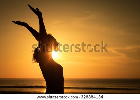 woman open arms under the sunset at sea. Concept of healthy life. - stock photo