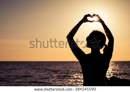 woman open arms under the sunset at sea. Concept of healthy life.