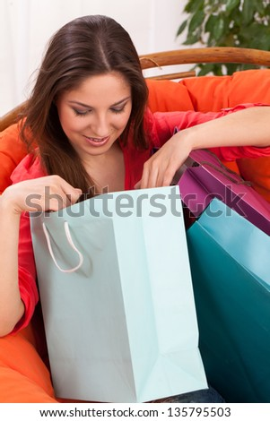 Woman open shopping bags at home sitting on the chair